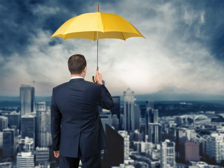 Businessman with yellow insurance umbrella looking over city