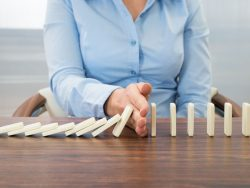 Close-up Of Businesswoman Stopping The Effect Of Domino With Hand