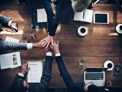 High angle view of businesspeople over boardroom table collaborating celebrating