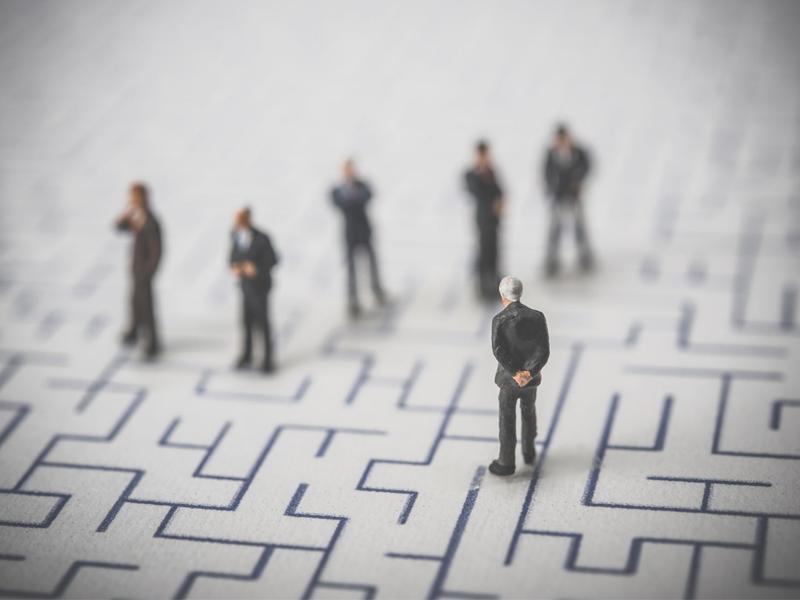 Miniature of business men observing maze risk concept