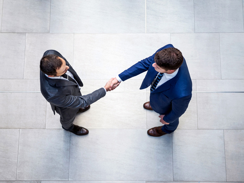 Overhead view of young business men shaking hands