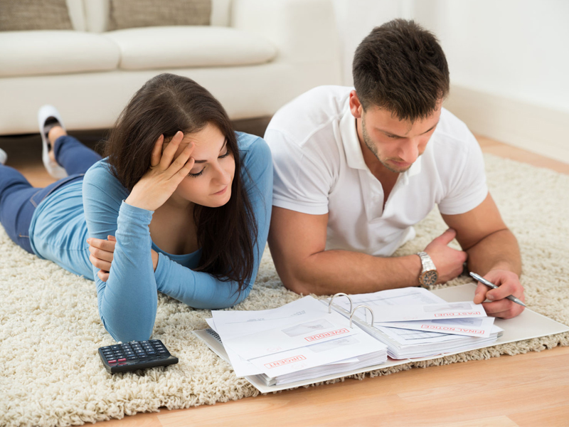 Worried Young Couple Lying On Carpet Calculating Their savings, planning future, retirement fund
