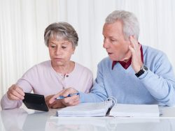 stressed senior couple calculating budget at home