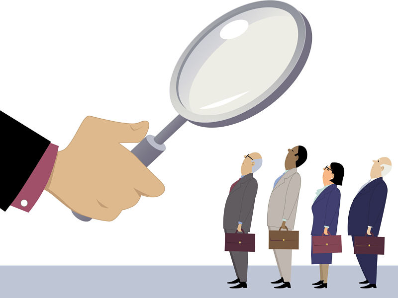 business people standing in line under a magnifying glass