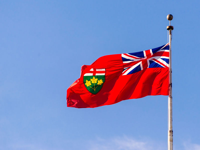 flag of ontario flying high on a flag post, against blue sky