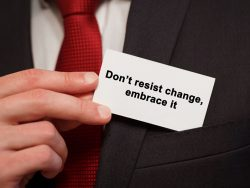 usinessman putting a card with text don't resist change embrace it in the pocket