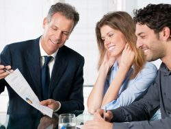 happy young couple discussing with a financial agent