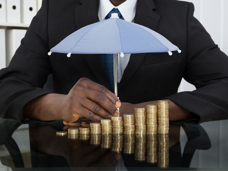 businessman protecting stack of coins with umbrella at desk