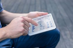 Casual person using tablet to analyse financial dashboard