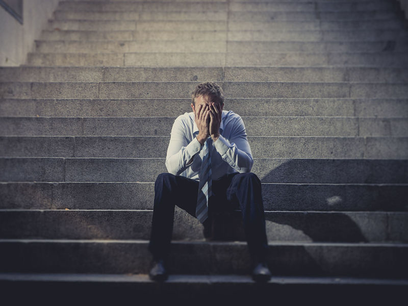 Depression, business man sitting on ground street concrete stairs suffering emotional pain,