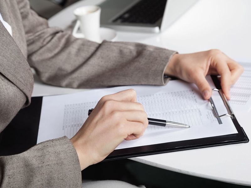 16253748 - hand of a businesswoman at her desk with a pen and a clipboard