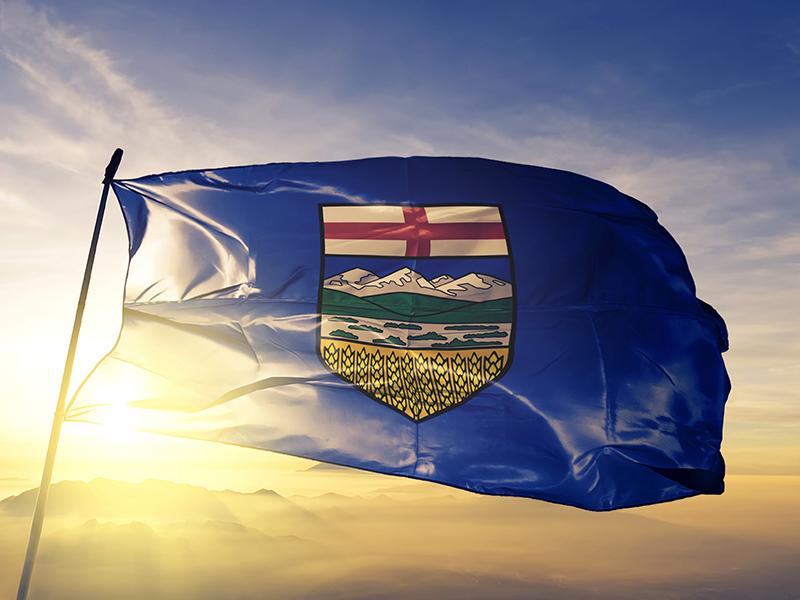 Alberta flag in front of setting sun