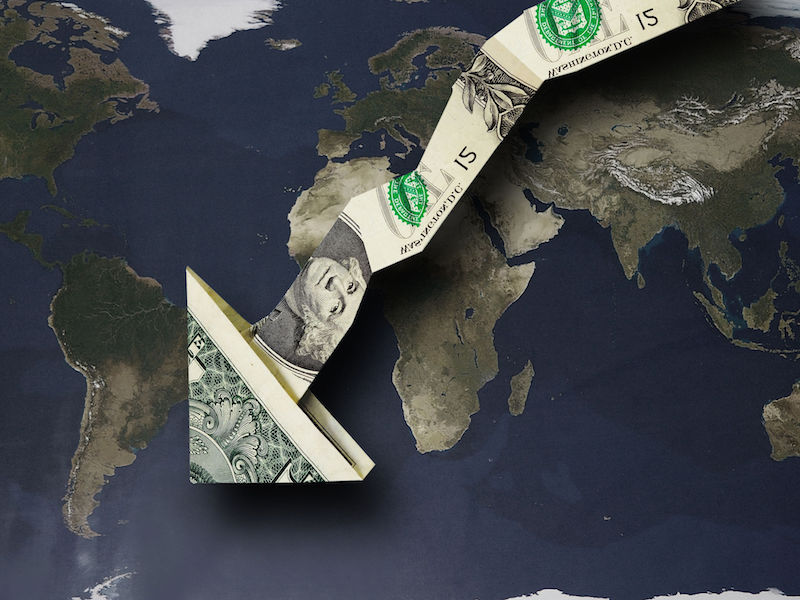 Origami dollar arrow pointing down over a world map