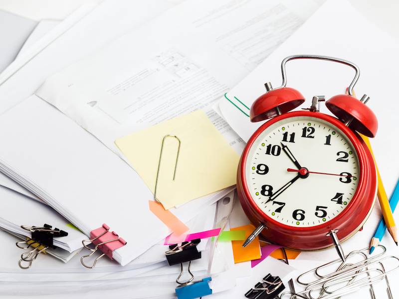 Time management concept. Composition with documents, stationary and alarm clock on table