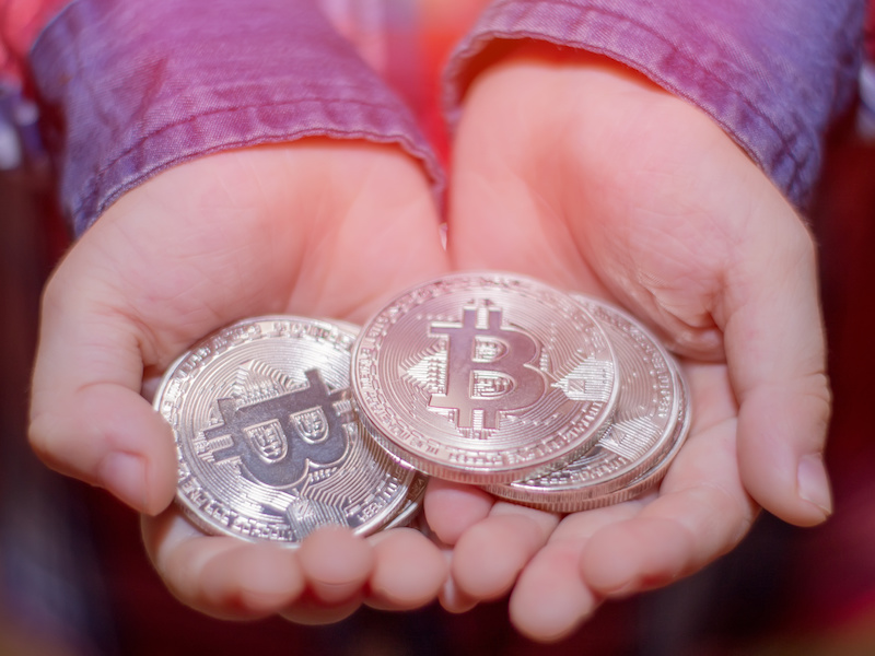 Bitcoin in the hands of a child. The boy holds a metal coin of crypto currency in his hands.