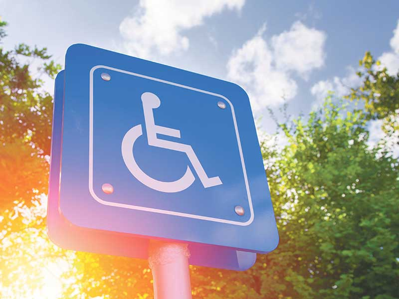 Disability sign, white wheelchair graphic on blue background