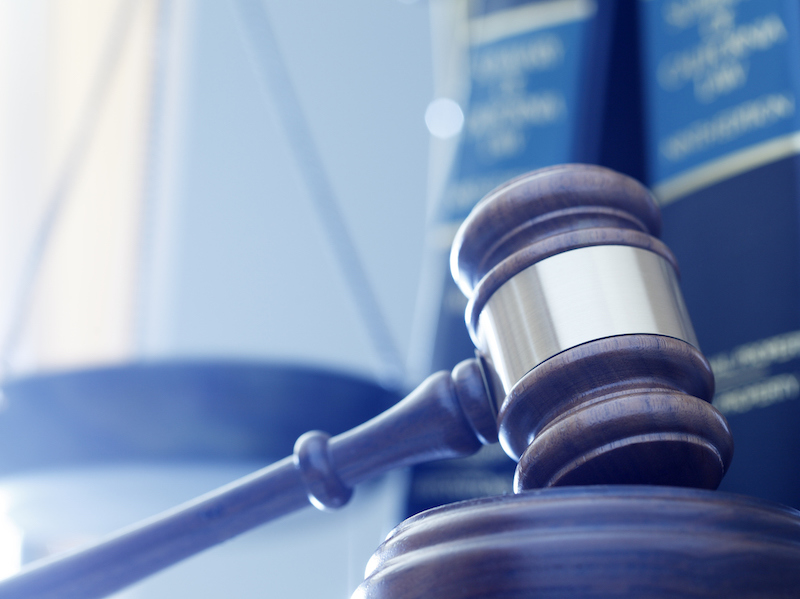 A gavel rests on its sounding block with a several law books and a justice scale out of fucus in the background. A cool blue cast dominates the scene. (A gavel rests on its sounding block with a several law books and a justice scale out of fucus in t