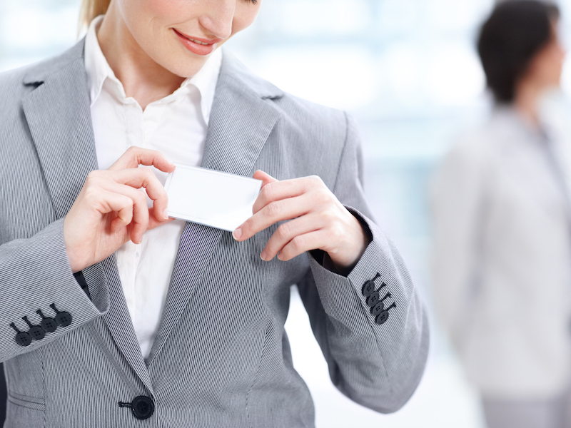 Cropped image of a smiling businesswoman pinning her name tag on her jacket - copyspace