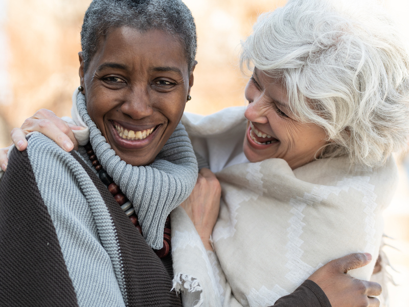 Two senior friends laugh affectionately together. The women are standing outside on a sunny but cool day. They are dressed in casual sweaters. One woman is of African descent and the other is Caucasian.