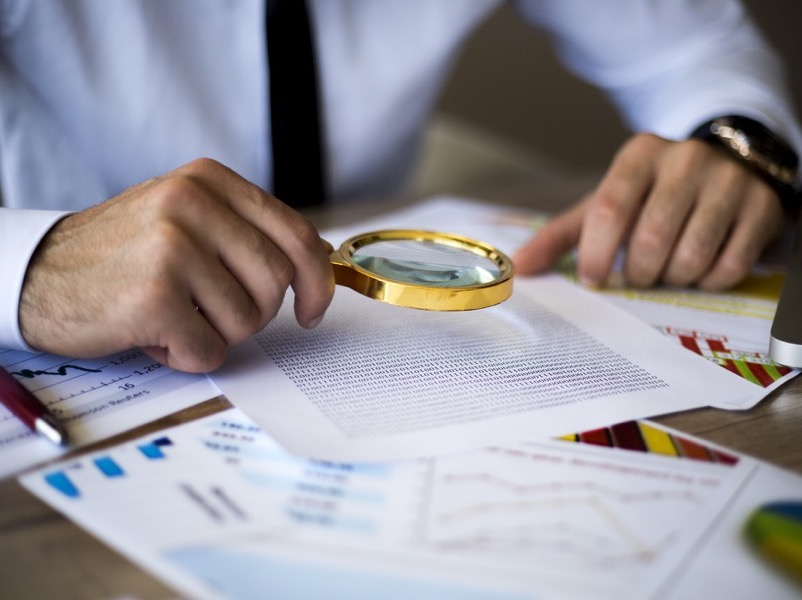 business man using magnifying glass to inspect documents