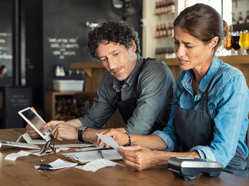 Man and woman sitting in cafeteria discussing finance for the month. Stressed couple looking at bills sitting in restaurant wearing uniform apron. Cafe staff sitting together looking at expenses and bills. (Man and woman sitting in cafeteria discussi