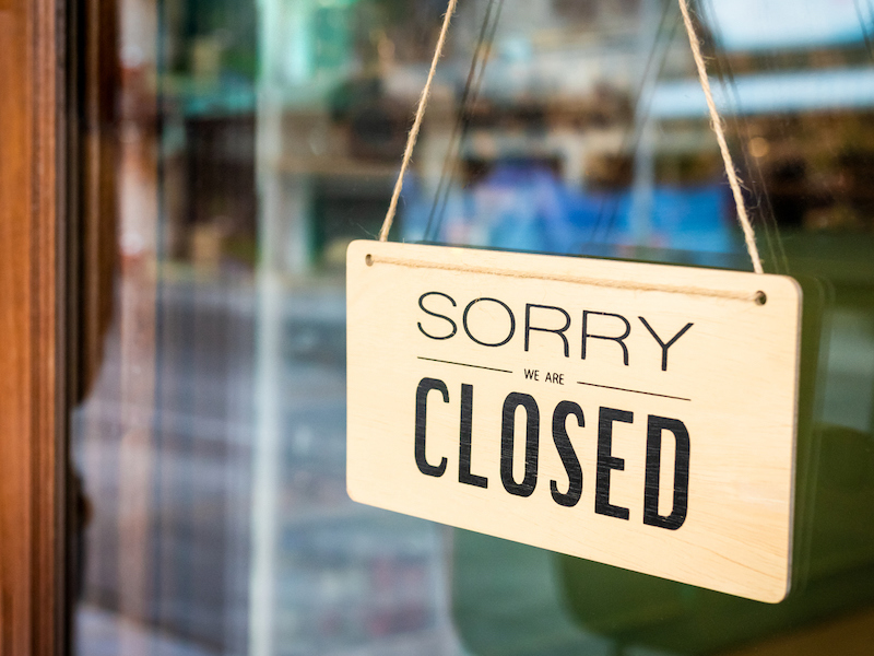 Sorry we are closed sign board hanging on a door of cafe