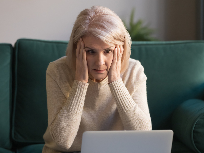 Shocked middle aged mature woman feeling stressed reading unbelievable online news, surprised senior old lady looking at laptop amazed by unexpected stuck computer problem sit on sofa at home (Shocked middle aged mature woman feeling stressed reading